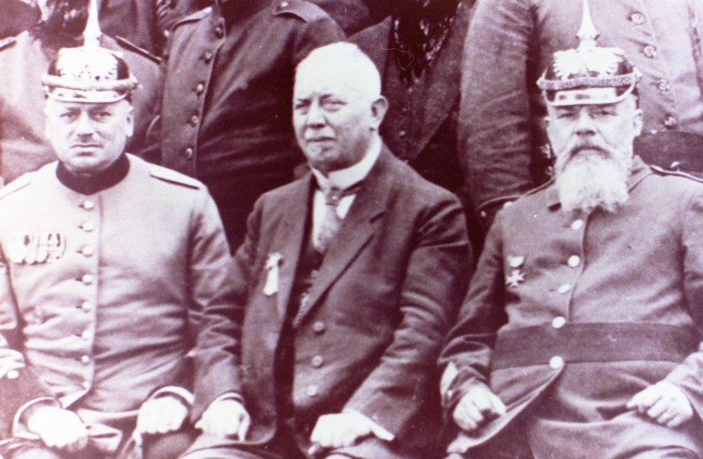 Mit Pickelhaube und Ehrenauszeichnungen an der Brust posieren Ehrenbrandmeister Herman Krebs und Oberbrandmeister Gustav Reckmann. In der Mitte des Bildes von 1928 sieht man Altbürgermeister Bernhard Lappe